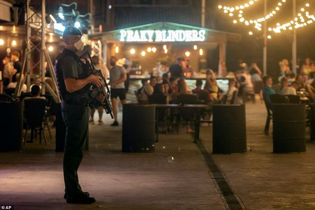 A Spanish Guardia Civil officer watches over revellers in Magaluf as the country tries to balance reopening beachfront bars with protecting against a deadly second wave of cases