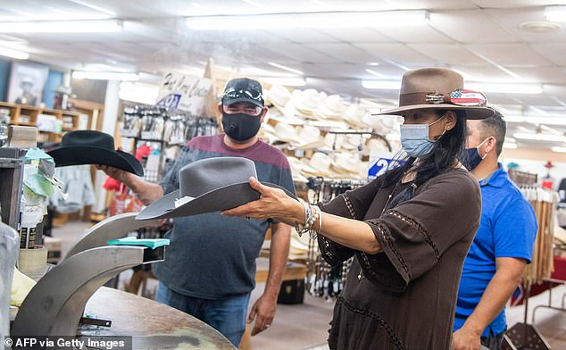 A woman shapes a Stetson hat in front of customers while wearing a mask at the manufacturing store on Saturday in Garland, Texas amid the coronavirus pandemic