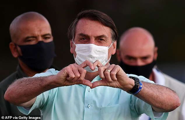 Brazilian President Jair Bolsonaro gives a heartfelt gesture to supporters outside Alvorada Presidential Palace in Brasilia last night as he remains positive for Covid-19