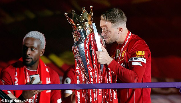 Henderson kisses Premier League trophy after receiving it from Sir Kenny Dalglish