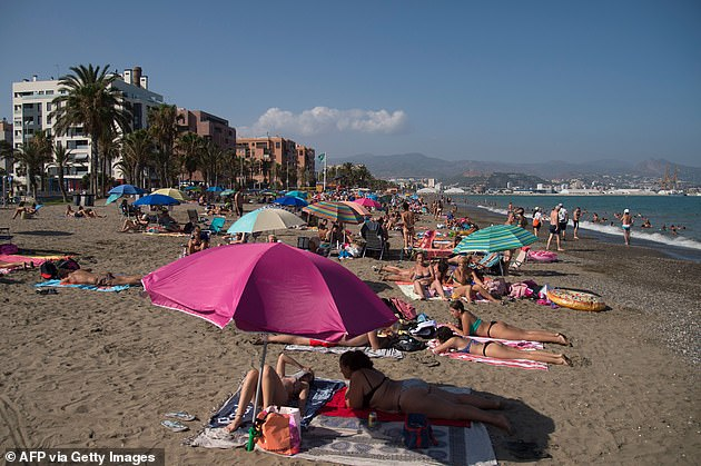 People sunbathing at the La Misericordia Beach, Malaga, this week as the Spanish tourism industry faces uncertainty