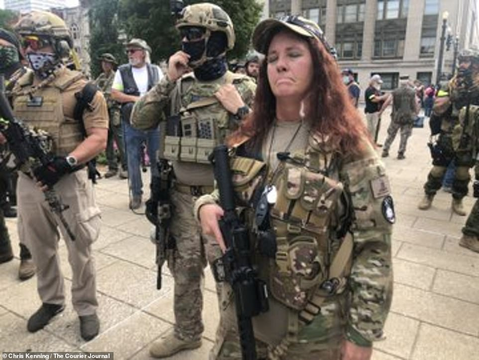Members of the Kentucky Three Percenters militia are seen above lining up outside city hall in Louisville, Kentucky, on Saturday