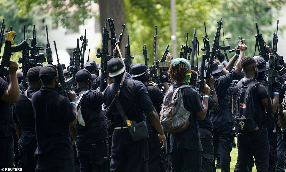 NFAC militia members aim their weapons skyward as they prepare to march toward Jefferson Square Park in Louisville, Kentucky, on Saturday