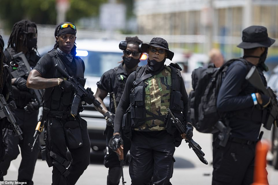 Grandmaster Jay is seen second from right leading militia members on a march toward City Hall in Louisville on Saturday