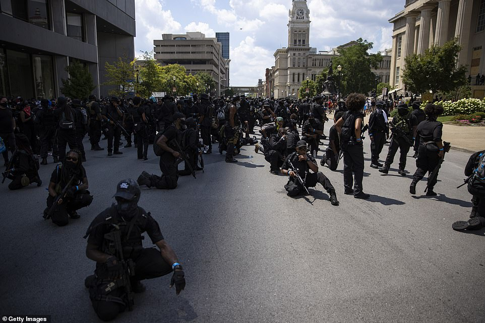 Members of NFAC rest after a march toward City Hall in downtown Louisville, Kentucky, on Saturday