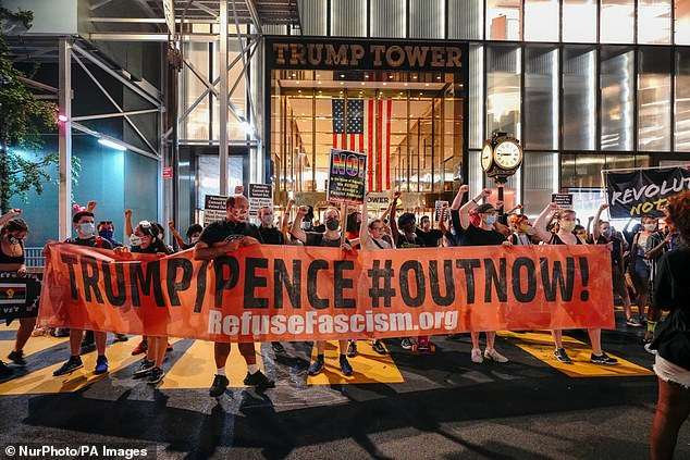 Protesters carried a banner saying 'Trump/Pence #OutNow' at Saturday's protest