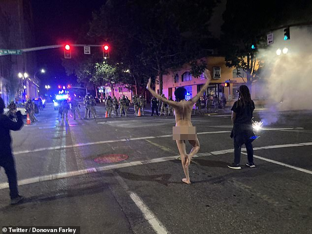 Jen struck a series of ballet and yoga poses in front of anti-riot officers at around 1.45 am on Saturday morning