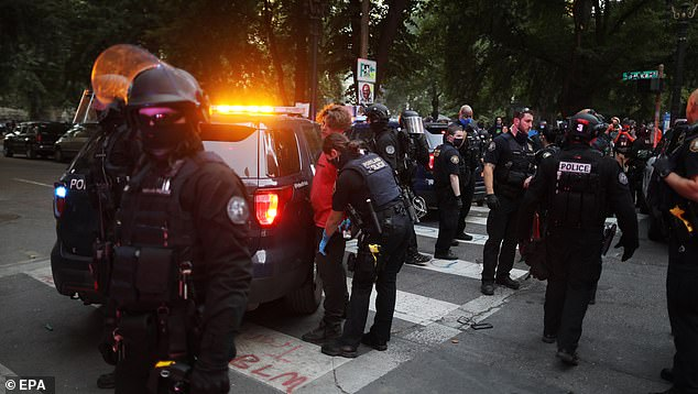 The city of Portland has seen daily Black Lives Matter protests decrying police brutality in the wake of George Floyd's death. Above, police escort a man in a red shirt out of Lownsdale Square following reports of shots fired on Sunday evening in Portland