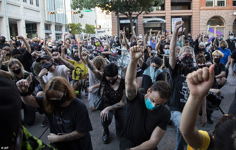 Protesters knee and raise their fists in a silent tribute to Foster, who was fatally shot in downtown Austin on Saturday night
