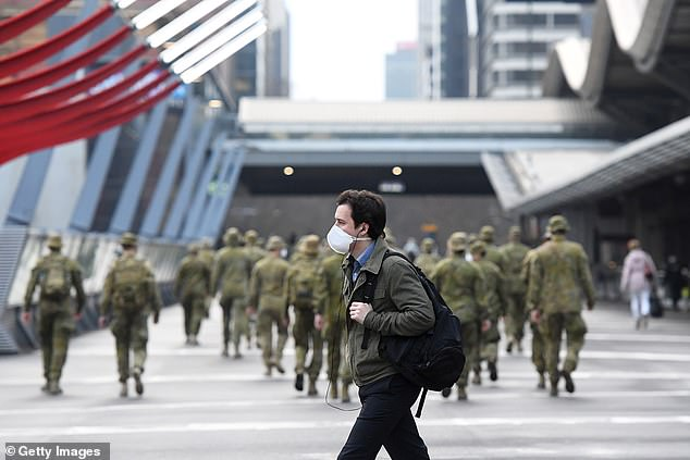 Masks are now compulsory in Melbourne and the Mitchell Shire. Pictured: a man walks through the Melbourne CBD on Monday in front of Australian Defence Force personnel on duty to help with the coronavirus response