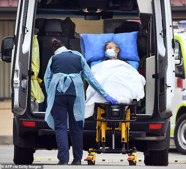 Ambulance officers remove a resident from the St Basil's Home for the Aged in the Melbourne suburb of Fawkner on Monday