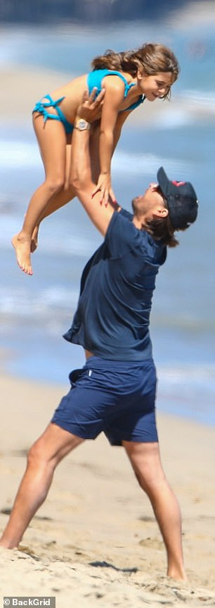His baby girl: At one point in their shoreline hangout, Scott picked up a squirmy Penelope from the sand and lifted her over his head
