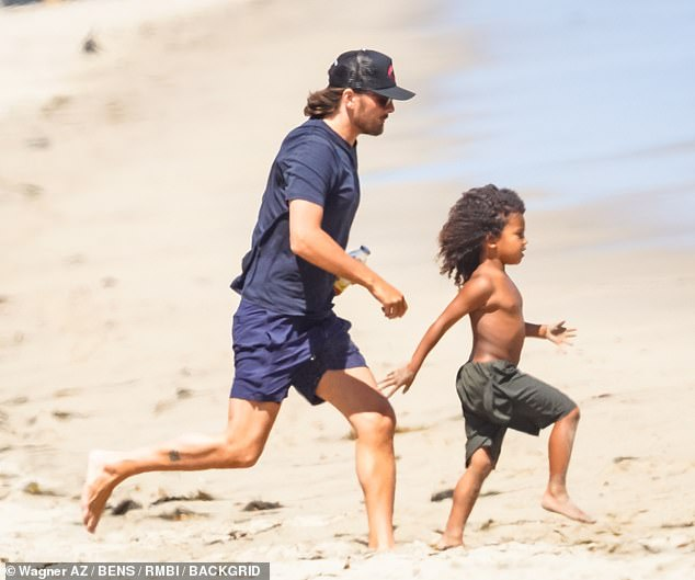 Bonding: Saint was clearly loving all the quality time he was spending with Scott as he ran around in the sand in a pair of black board shorts