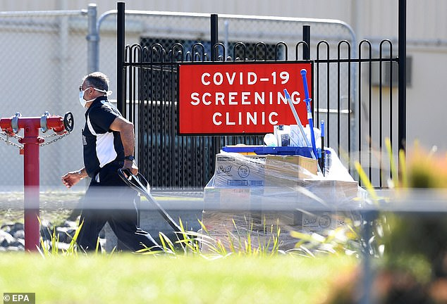 A man delivers cleaning equipment to a COVID-19 screening clinic at the Parklands Christian College in Logan