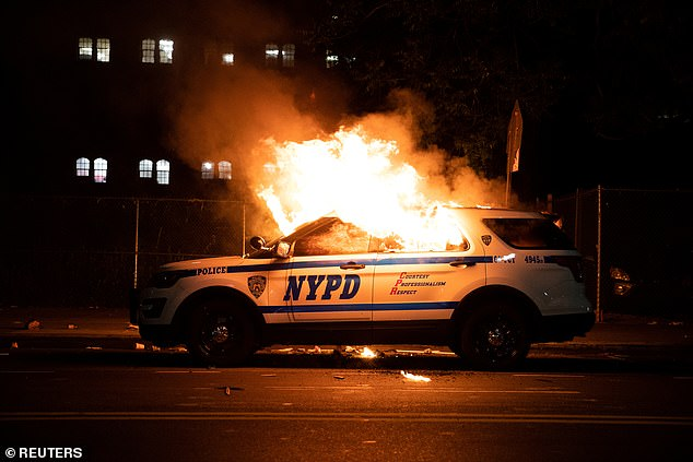 A squad car is seen set ablaze in Brooklyn on May 30, 2020. Mayor de Blasio proceeded to slash billion from the NYPD budget