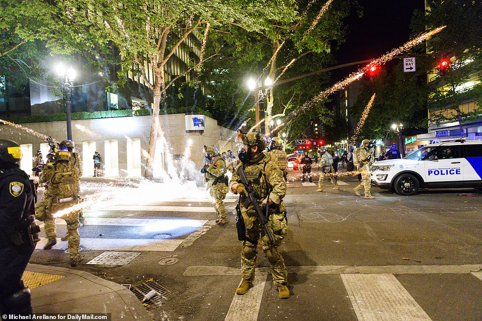 A mortar round thrown by protesters explodes amidst federal officers in downtown Portland Tuesday night