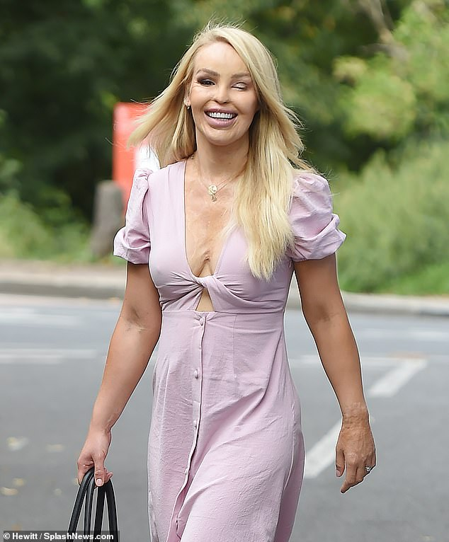 Smile:The TV personality, 36, looked sensational in a plunging pastel pink dress with a cut-out detail as she enjoyed a stroll