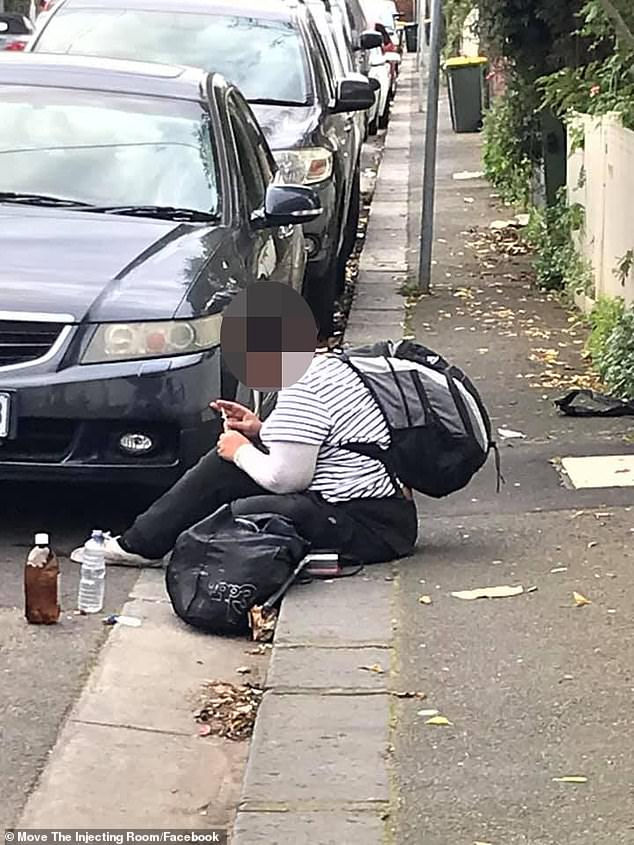 A drug user is pictured injecting drugs on a inner-city street in Melbourne's North Richmond