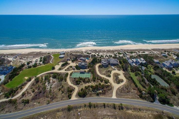 As well as the mansion (seen on the right-hand side), there are two smaller structures with tennis courts and a swimming pool (center) and a golf course with two putting greens (right) and two golf cottages. All overlook the Atlantic Ocean