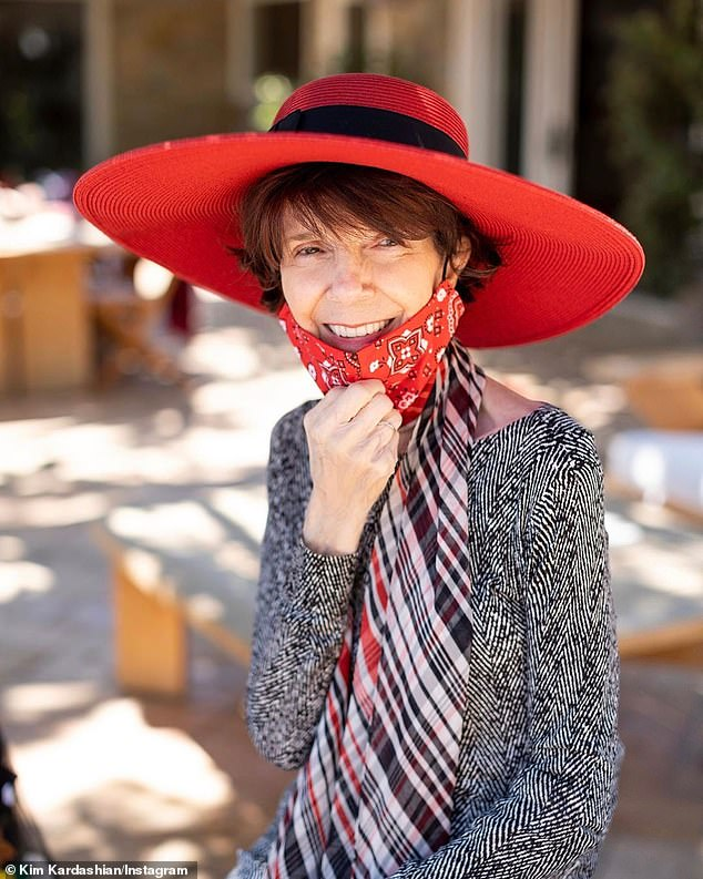 Birthday girl: Mary Jo looked stylish in a long sleeve dress, plaid scarf and a paisley face mask and matching red hat