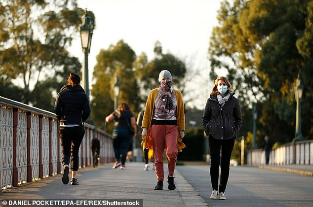 Melbourne residents pictured wearing masks on a walk along Morell Bridge on July 24