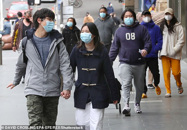 Only supermarkets, pharmacies and service stations are expected to operate in a normal capacity (people wearing masks in Melbourne pictured on July 19)