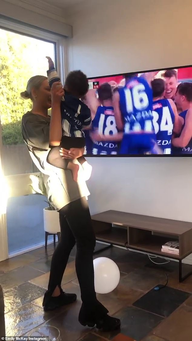 McKay holds her son's hand up as they cheer on Daw following his first goal since returning to AFL