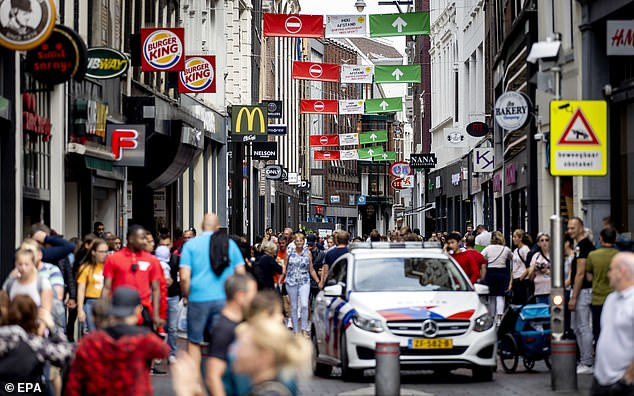 Holland, a country of 17 million people, has seen 6,147 pandemic deaths after adopting what it called 'intelligent lockdown'. Pictured, touristson the Nieuwendijk in Amsterdam on July 23
