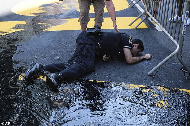 For about 30 seconds, the officer writhed in pain on the street after slipping and seeming to hurt his arm or head