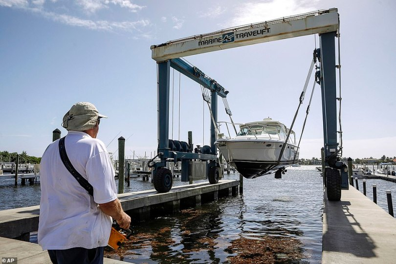 Brett Hand controls a Marine Travelift with a hand held remote to lift boats out of the water and move them onto the grounds of Palm Beach Yacht Center for safe keeping as Hurricane Isaias approaches the Florida coast Saturday