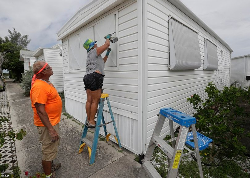 Chris Nagiewicz, left, watches as his wife Mary screws in a hurricane panel on Saturday on a trailer home in Briny Breezes, FL