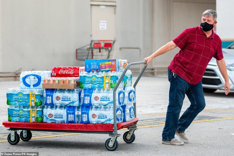 A Fort Lauderdale resident stocks up with groceries and water in preparation for Hurricane Isaias on Friday
