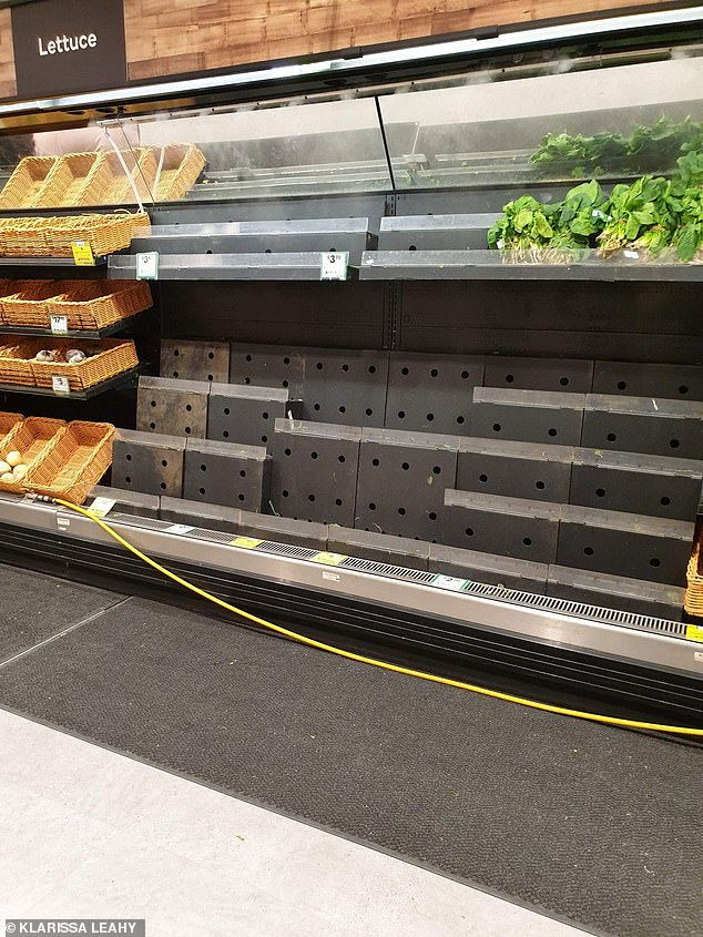 Nearly empty shelves are seen in the vegetable section of a Melbourne supermarket on Sunday