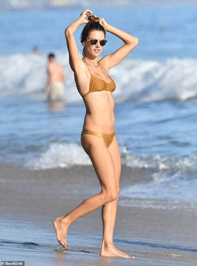 Glowing: Alessandra was sporting a noticeably makeup-free, glowing complexion as she made her way from the water to the sandy shore