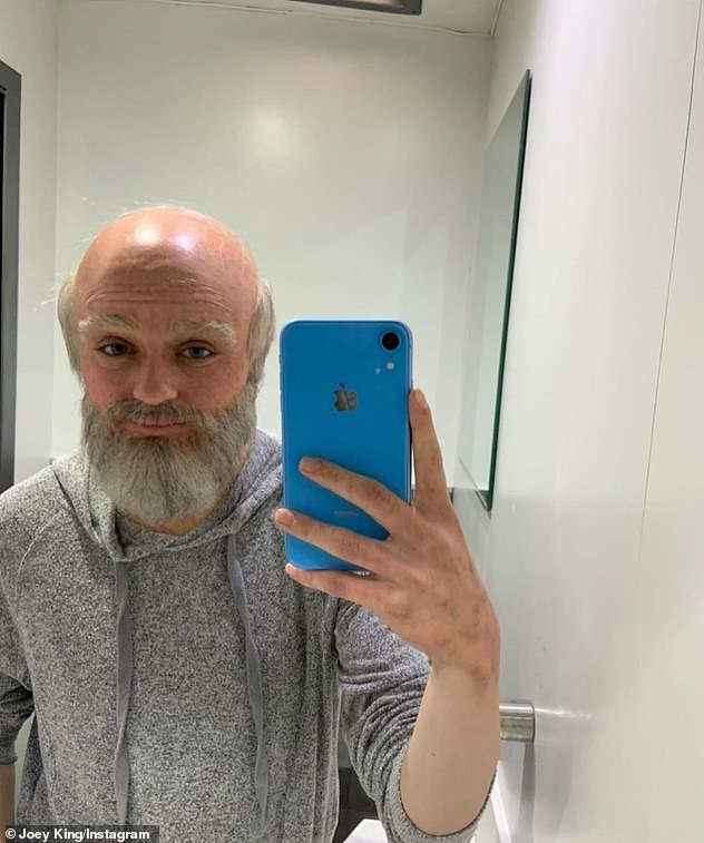 Old man: Another shot inexplicably showed Joey wearing a bald cap with a grey beard and a grey hoodie, taking a mirror selfie