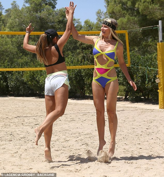 Sensational:Caprice, 48, was flaunted her figure once again in a colourful cut-out swimsuit as she enjoyed a game of volleyball with her pals in the sunshine on Monday