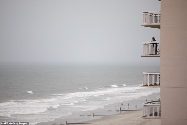 A man observes the dark clouds and high surf produced by Hurricane Isaias from the balcony of his hotel in North Myrtle Beach, South Carolina, on Monday
