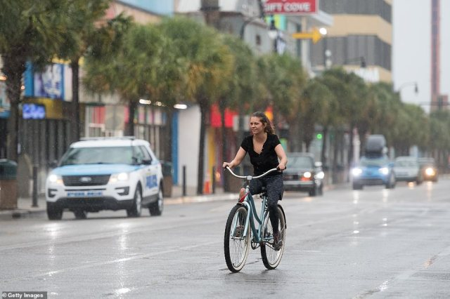 A young woman rides a bicycle in the rain on Ocean Boulevard hours before Hurricane Isaias made landfall near Myrtle Beach, South Carolina, on Monday