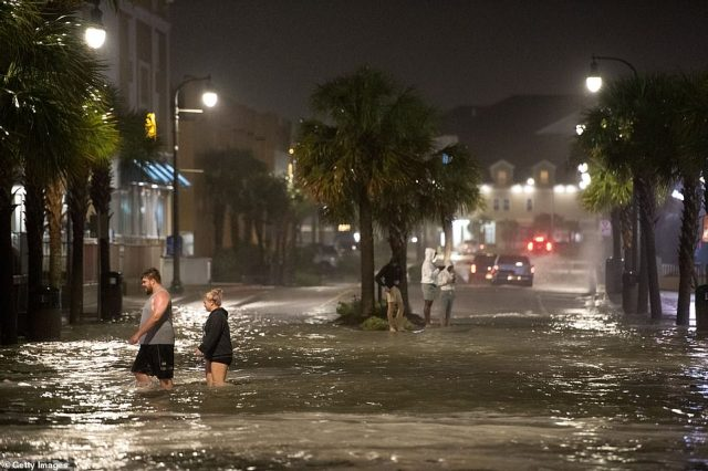 People walk through flood-hit Ocean Boulevard in Myrtle Beach, South Carolina, late on Monday after Hurricane Isaias made landfall