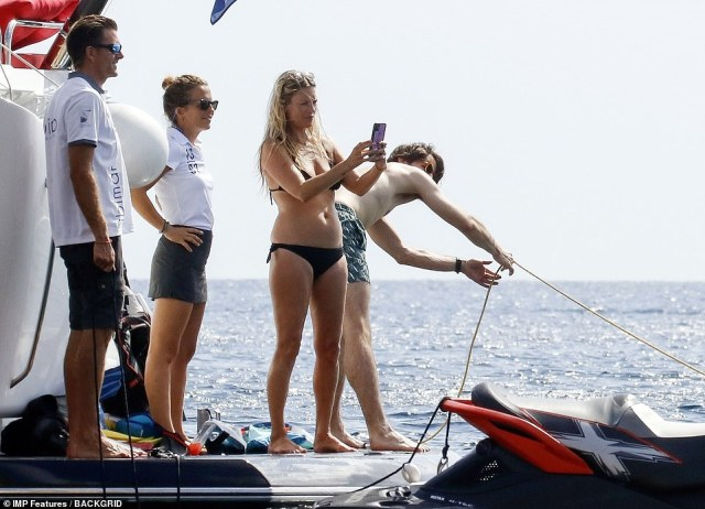 Following in her footsteps: Kate couldn't resist taking plenty of photos of her daughter as the yacht crew looked on