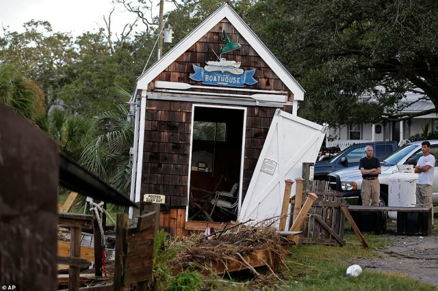 In other parts of North Carolina, photos showed damage to buildings, marinas and businesses after wind and rain lashed areas like Southport, NC (pictured) when the hurricane hit at 11pm Monday night