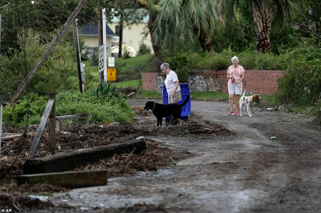 Residents survey the damage following the effects of Hurricane Isaias in Southport, NC, on Tuesday
