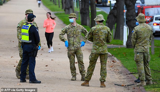 Melbourne is now enduring the country's most restrictive virus-control measures (Pictured: Police officers and soldiers patrol a popular running track in Melbourne)