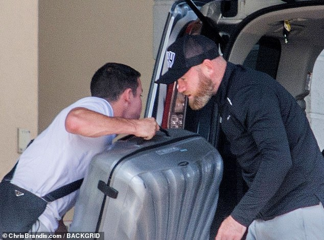 Homeward bound: Wayne Rooney was at hand to help his brother-in-law with his luggage as he lifted his suit cases into a van before leaving the family trip to Barbados