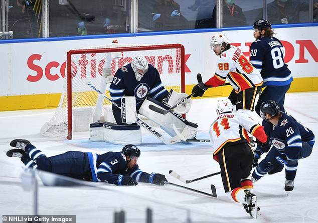 After the puck ricocheted in front of the Winnipeg net, Calgary's Mikael Backlund (No. 11 in white) launched a slap shot in front of the diving Poolman (left). Unfortunately for the 6-foot-3, 210-pound defenseman, the puck snuck under his visor and appeared to strike him on the chin