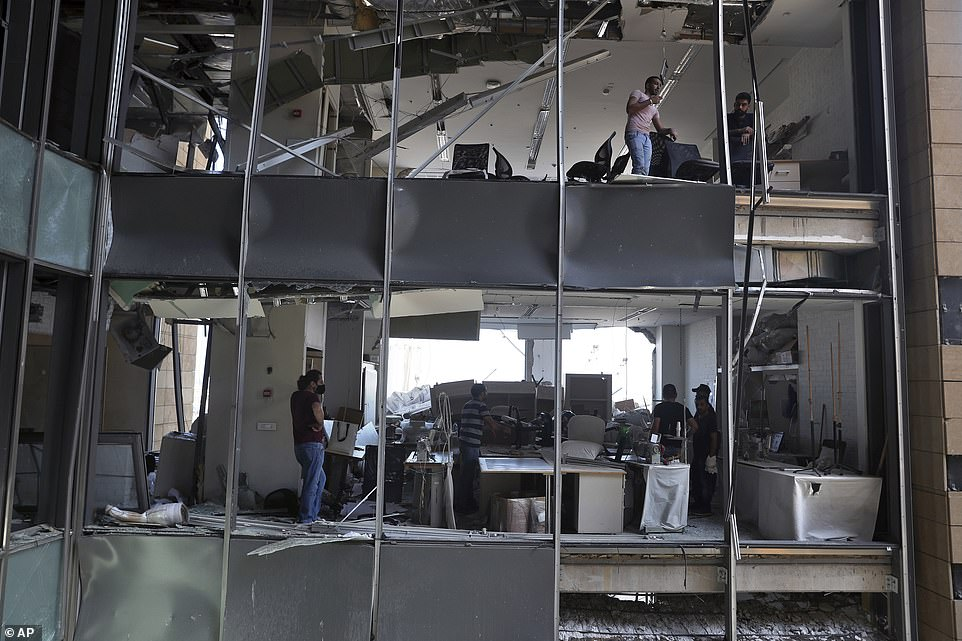 People pick their way through the remains of their destroyed office building after a massive explosion in Beirut