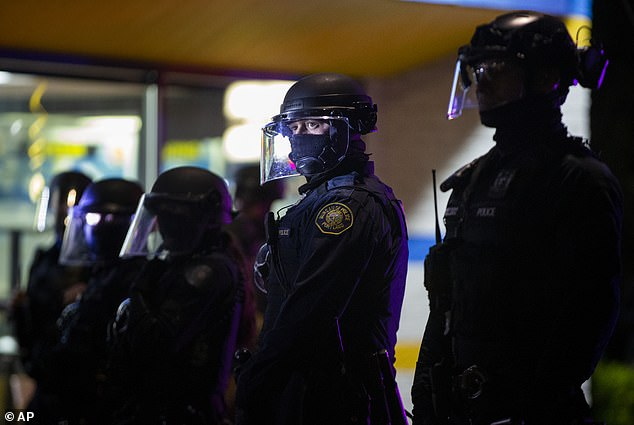 Pictured: Police stand by during a protest in Portland on Tuesday. Police have arrested more than 400 people since late May according to Portland Police Chief Chuck Lovell