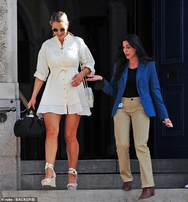 Steady! As she headed down the stairs, Vogue needed a helping hand to stay upright in her towering wedges