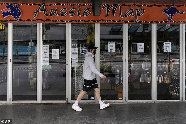 A Melburnian walks past a closed up shop on Wednesday as the city goes into stage four lockdown