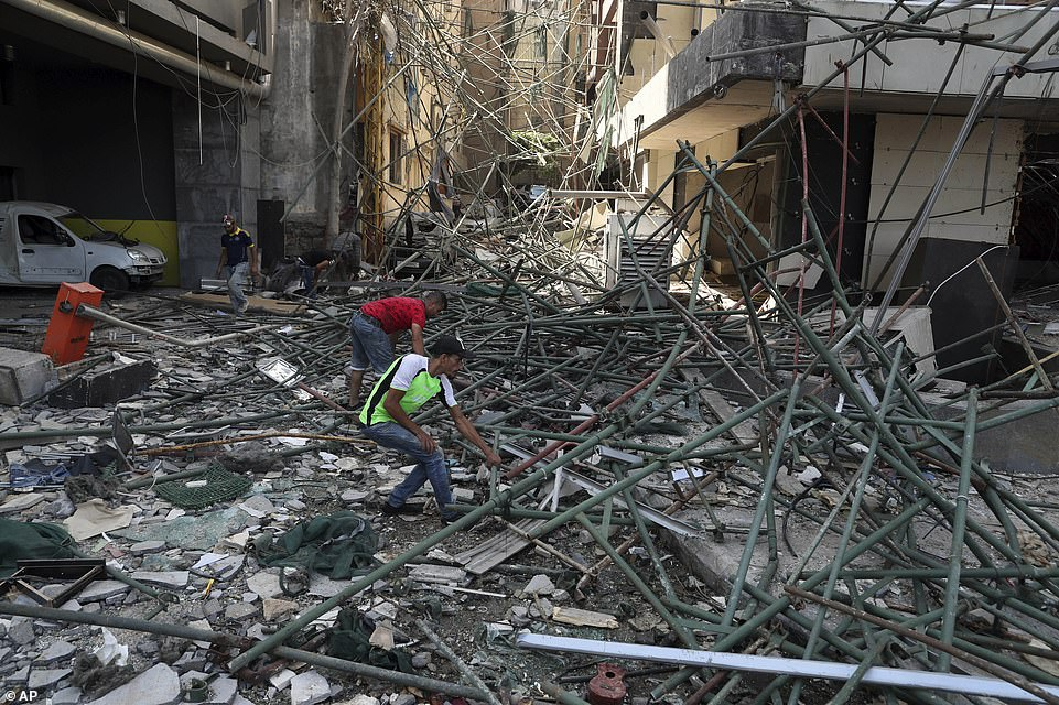 Workers remove rubble from damaged buildings near the site of an explosion which brought devastation to central Beirut